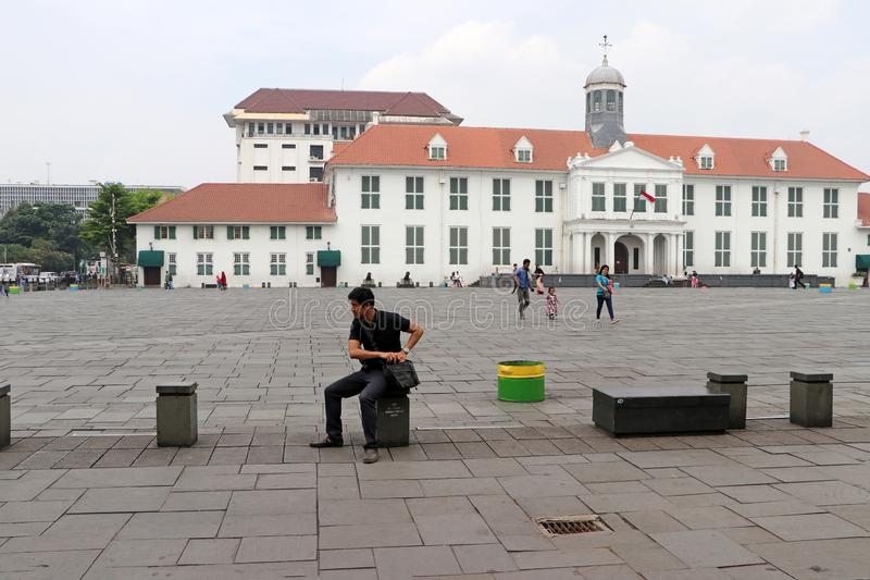 Dutch colonial building with people sitting and locals walk through Fatahillah Square in Old Town, Jakarta stock photo