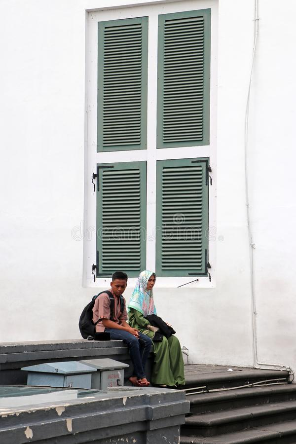 Muslim male and female teenagers sitting together beside the green window at Fatahillah Square in Old Town, Jakarta stock image