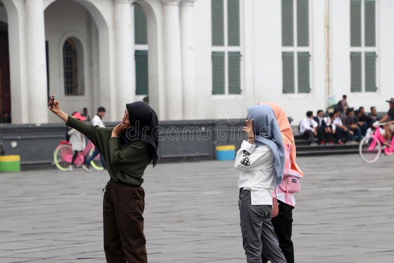 Three Muslim women Indonesian Selfie by smartphone in the Fatahillah Square at old town neighborhood in Jakarta. Jakarta, Indonesia May 6, 2019: Three Muslim stock photo