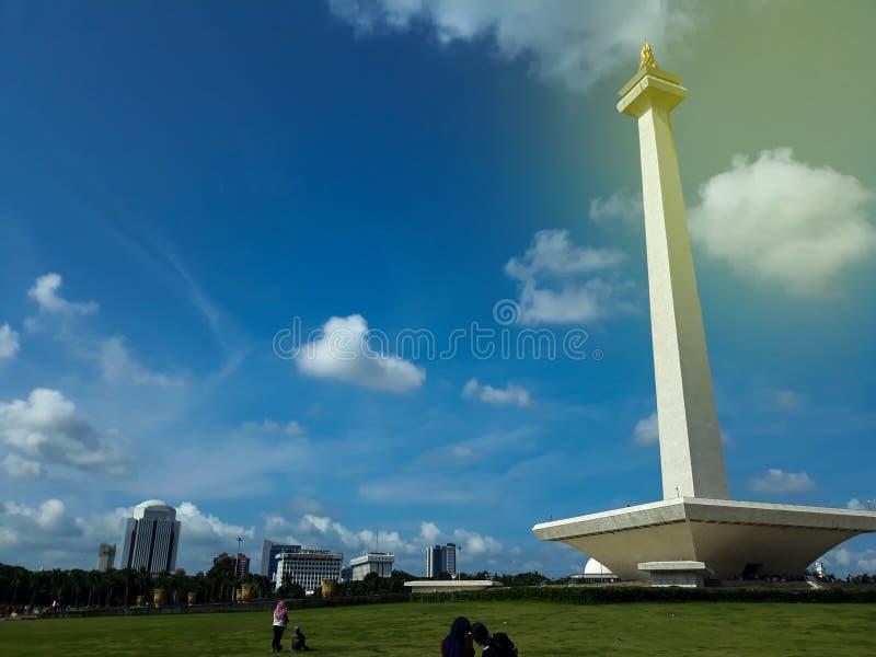 JAKARTA INDONESIEN - APRIL 29, 2019: Moln flyger över Monas eller den nationella monumentet En historisk gränsmärke som förläggas royaltyfri bild