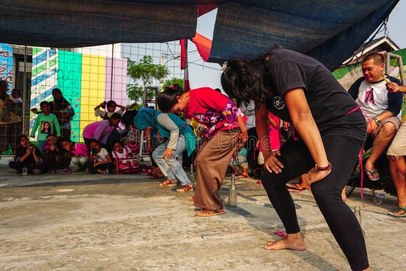 Jakarta Indonesien - Augusti 17, 2018: unga mödrar springer för att sätta spikar in i flaskor på indonesisk självständighetsdagen arkivbilder