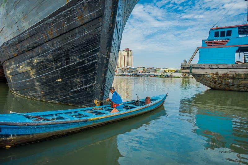 JAKARTA INDONESIEN - 3 MARS, 2017: Litet blått fartyg med lokalt lyckligt fiskaresammanträde inom och att förbigå framme av royaltyfria bilder