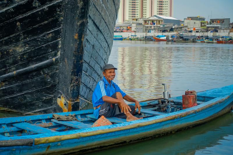 JAKARTA INDONESIEN - 3 MARS, 2017: Litet blått fartyg med lokalt lyckligt fiskaresammanträde inom och att förbigå framme av royaltyfria foton