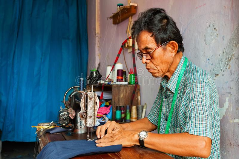 Portrait of senior tailor man at work royalty free stock images