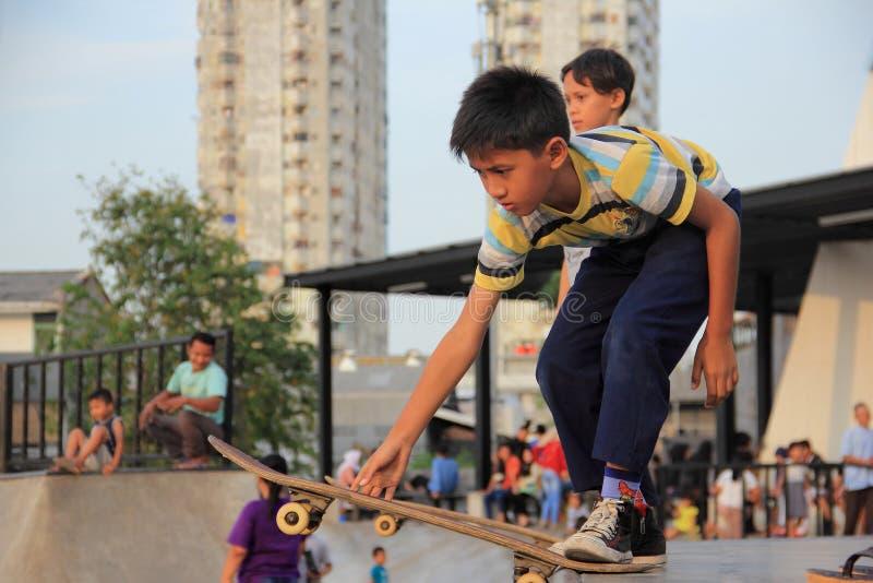 JAKARTA - Maj 27th, 2017 Ungar som spelar skateboarden på Kalijodo, J arkivfoto