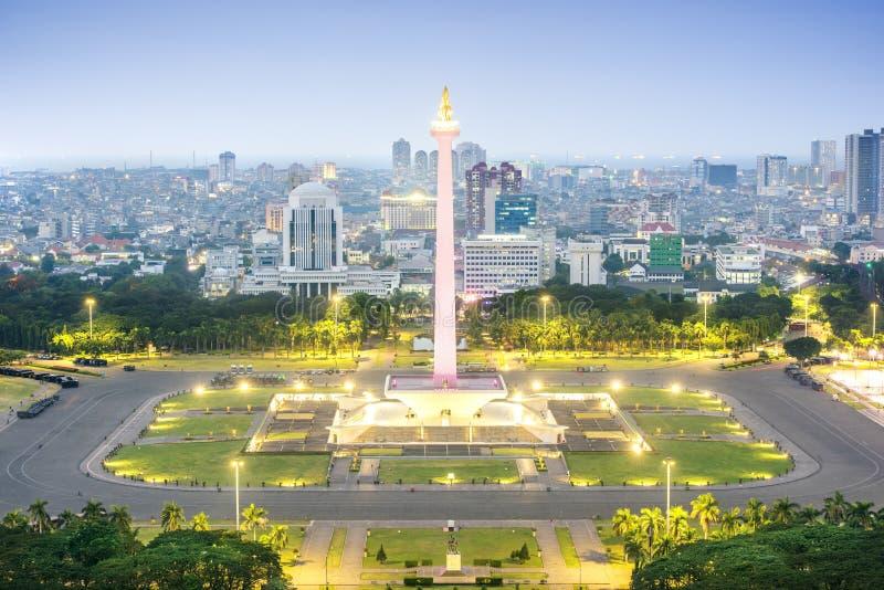 Jakarta stadshorisont med den nationella monumentet Monas för iconic symbolnågot liknande på natten royaltyfri fotografi