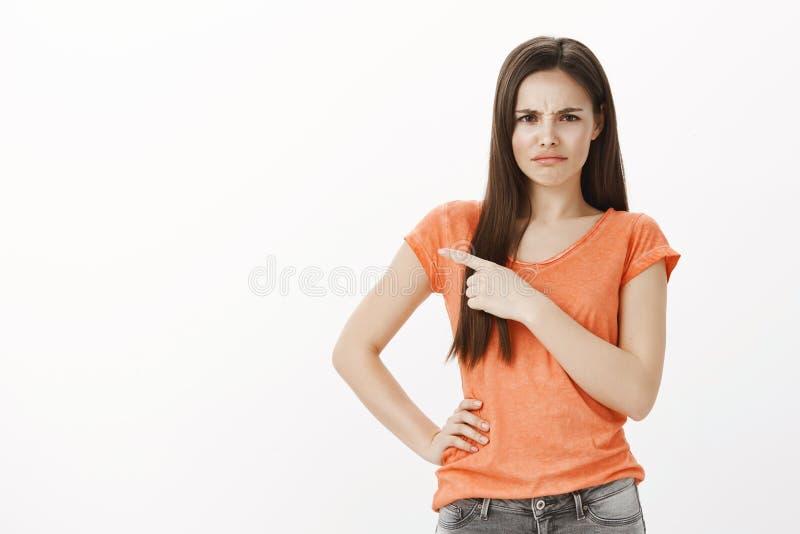Jaki okropna reklama Portret nieporuszona marszczy brwi młoda kobieta w przypadkowym stroju, wskazuje przy górną lewicą fotografia stock