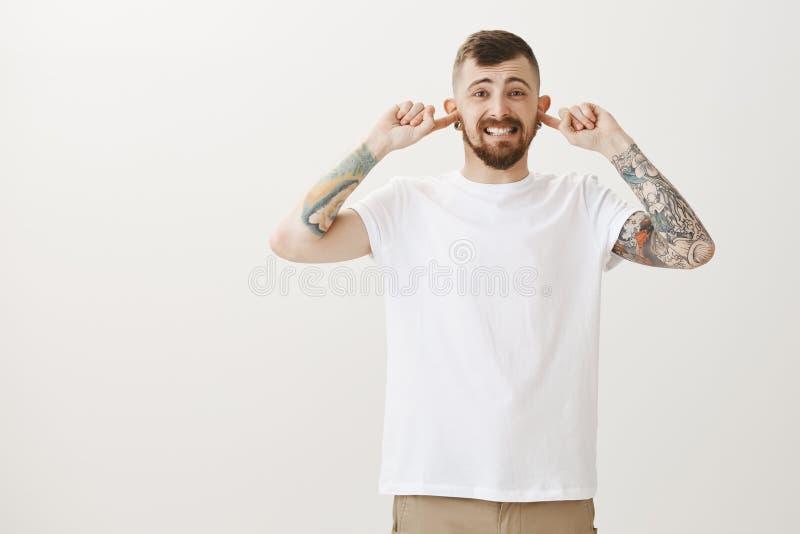 Jaki okropny hałas Studio strzał nierad niewygodny przystojny brodaty mężczyzna z tatuażami, nakrywkowi ucho z wskaźnikiem obraz stock