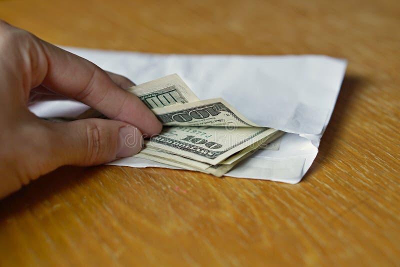 Jako symbol gotówkowy przeniesienie, mo męska ręka otwiera biały kopertowy pełnego Amerykańscy dolary USD, USA na drewnianym stol zdjęcie stock
