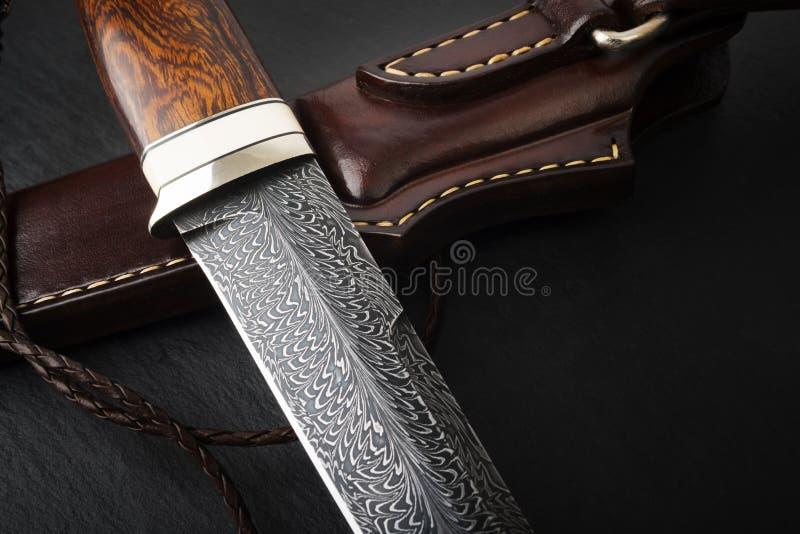 Jaktkniv från den Damascus mosaiken på en träbakgrund Handgjord läderskida arkivfoton