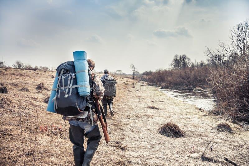 Jaktplats med jägare med ryggsäcken och jaktutrustning som går över landsbygd under jaktsäsong arkivbild