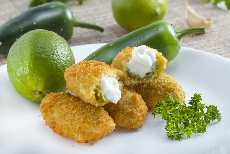 Jalapeno poppers. Mexican-american jalapeno poppers served with lime royalty free stock photo