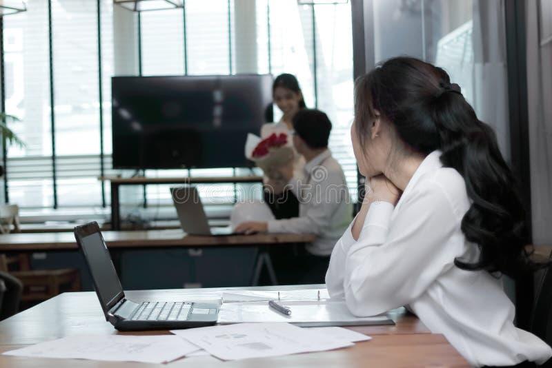 Jaloerse boze Aziatische bedrijfsvrouw die hartelijk paar in liefde in bureau kijken Jaloersheid en afgunst in vriendenverhouding stock afbeeldingen