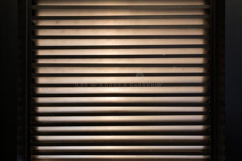 Jaloezie op venster Strepen van licht Het is donkere binnenkant stock foto's