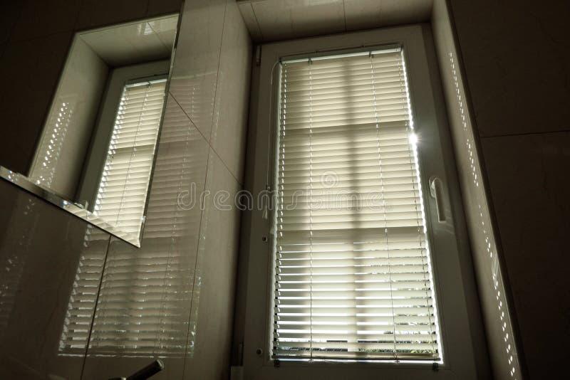 jaloezie venster in het toilet stock afbeelding