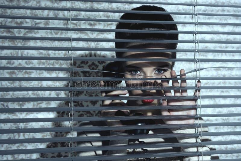 Jaloezievrouw dichtbij venster stock foto