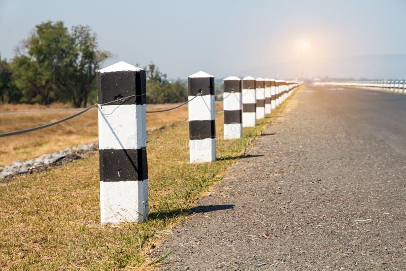 Jalones, jalones blancos y negros con el borde de la carretera de la hierba verde, foto de archivo