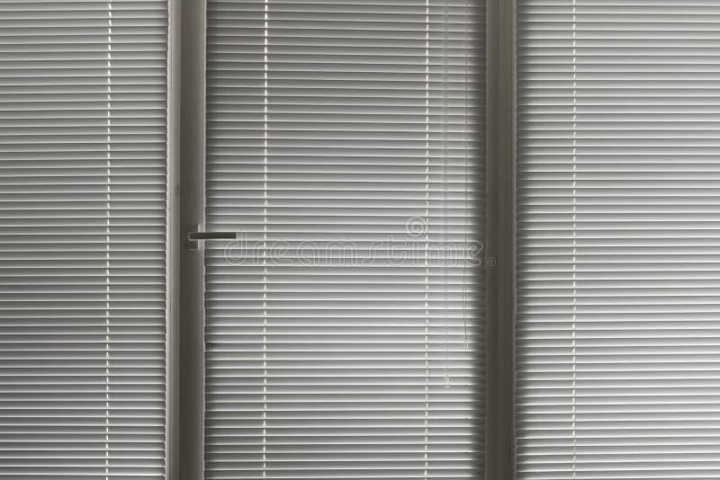 Jalousie horizontal cinzento na janela fotografia de stock