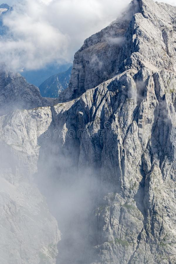 The Jalovec mountain ridge in clouds, part of Slovenia`s Julian Alps, during summer royalty free stock image