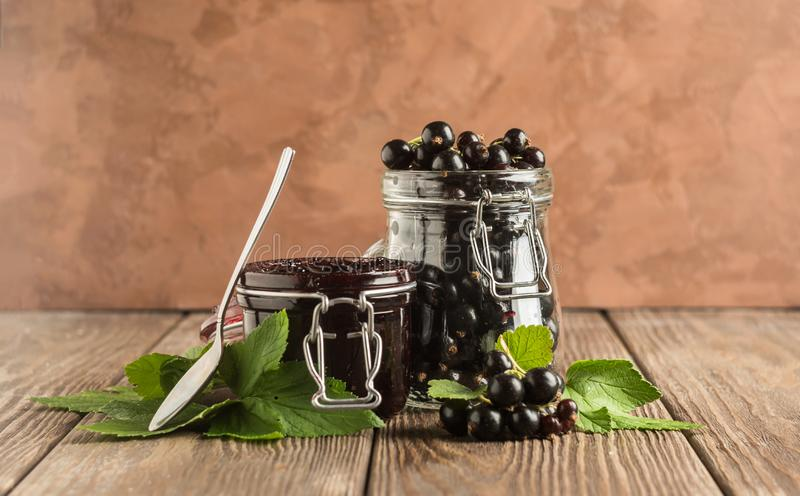 Jam and fresh black currant berries in glass jars stand on a wooden background. Horizontal frame. Selective focus. stock images