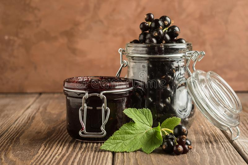 Jam and fresh black currant berries in glass jars stand on a wooden background. Horizontal frame. Selective focus. royalty free stock photography