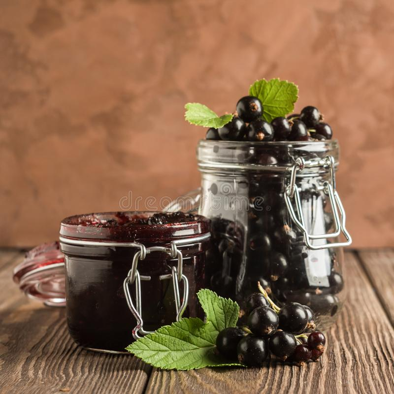 Jam and fresh black currant berries in glass jars stand on a wooden background. Square frame royalty free stock images