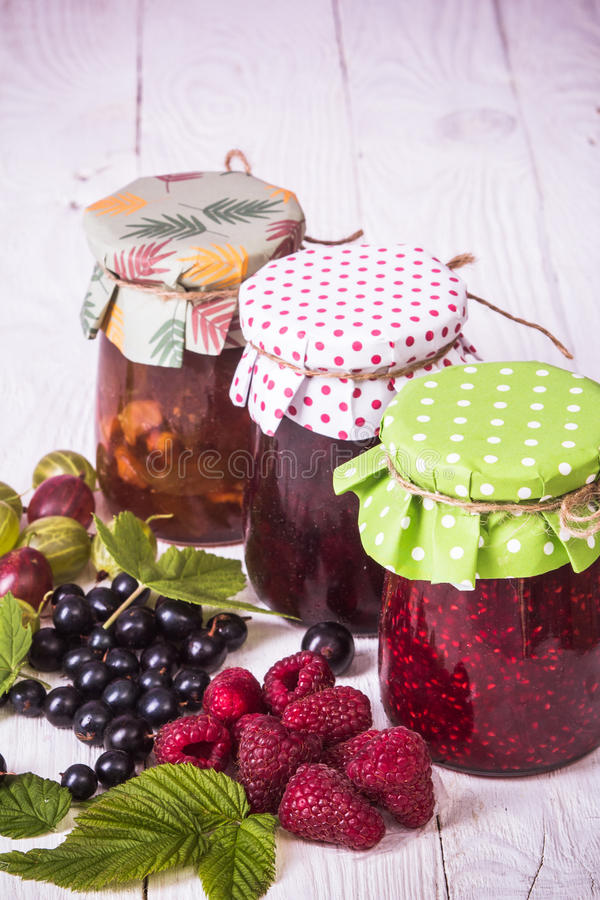 Jam in glass bank. Homemade jamand fresh currant, raspberries and gooseberries in jar on wood background. healthy organic and vegan food royalty free stock photos