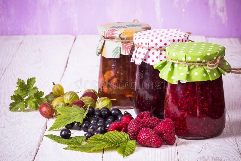 Jam in glass bank. Homemade jamand fresh currant, raspberries and gooseberries in jar on wood background. healthy organic and vegan food stock photo
