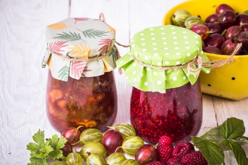Jam in glass bank. Homemade jamand fresh raspberries and gooseberries in jar on wood background. healthy organic and vegan food royalty free stock image