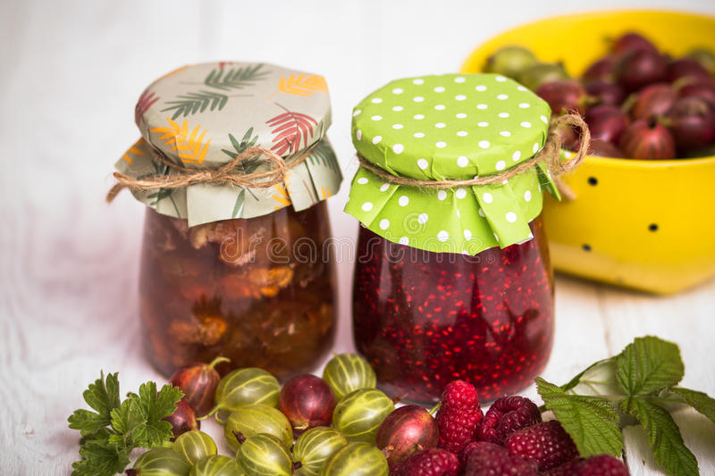 Jam in glass bank. Homemade jamand fresh raspberries and gooseberries in jar on wood background. healthy organic and vegan food royalty free stock photography
