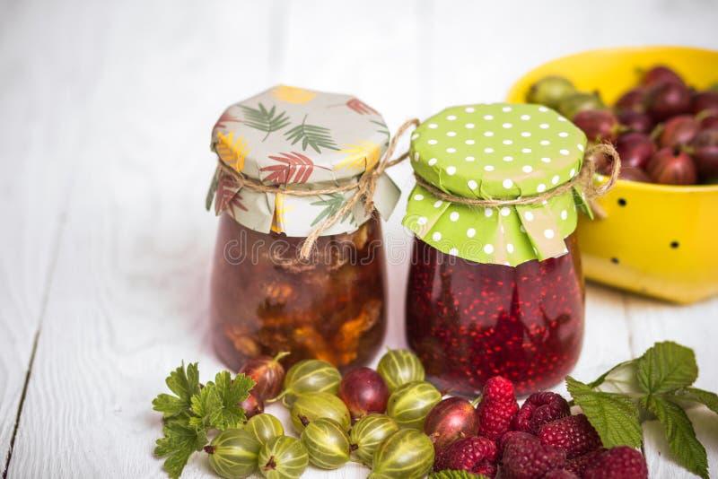Jam in glass bank. Homemade jamand fresh raspberries and gooseberries in jar on wood background. healthy organic and vegan food stock photo