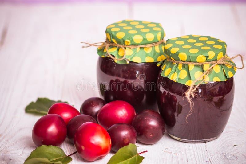 Jam in glass bank. Homemade jamand fresh raspberries and gooseberries in jar on wood background. healthy organic and vegan food stock photography