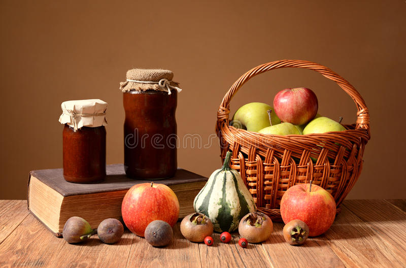 Jam into jars, books, and fruits in wicker basket royalty free stock image