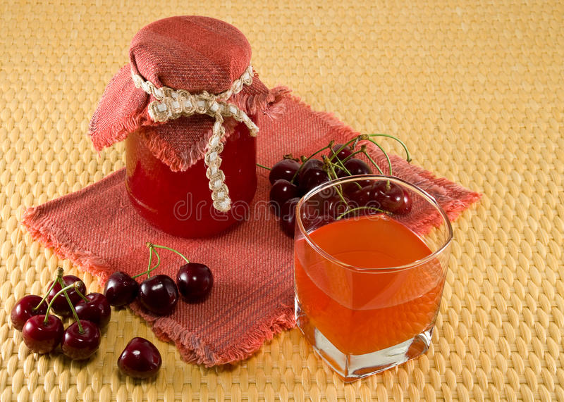 Jam and juice from cherries. Berries cherries, jam and juice on a napkin on the table royalty free stock photography