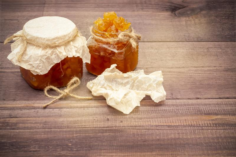 Jam from oranges, lemons, pumpkins. Jam on a spoon and in a jar on a wooden background. stock photography