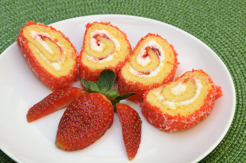 Jam roll cake slices. Decorated with strawberry on a green mat stock image