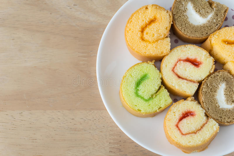 Jam roll cakes. A dish of jam roll cakes on wooden table royalty free stock photos