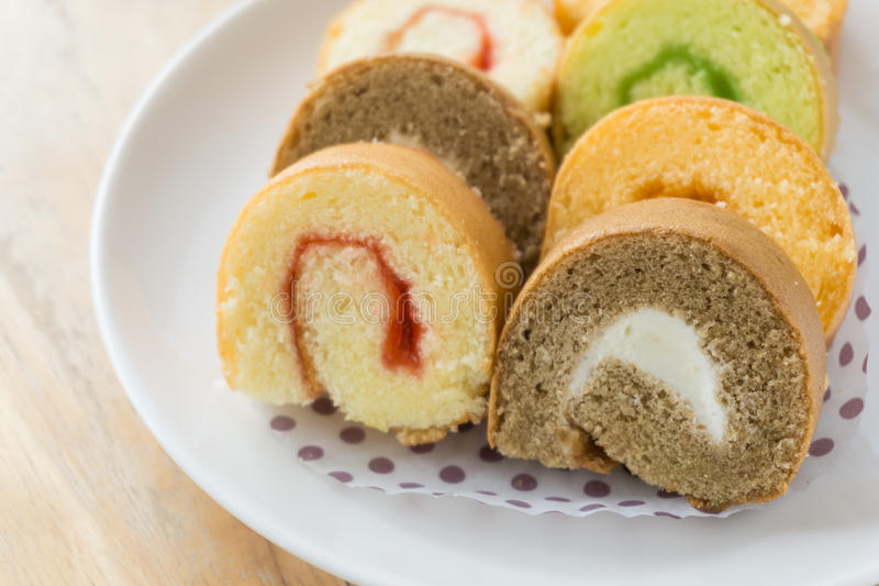 Jam roll cakes. A dish of jam roll cakes on wooden table stock photography