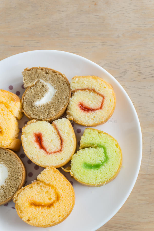 Jam roll cakes. A dish of jam roll cakes on wooden table stock images