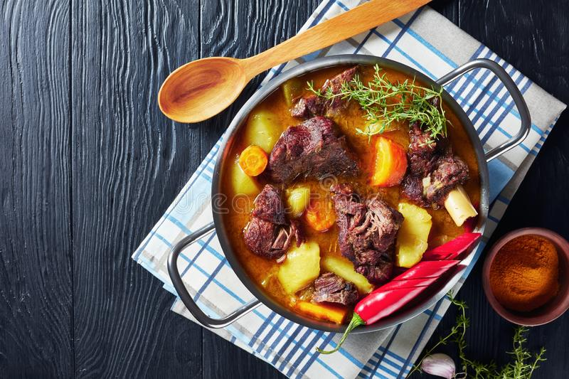 Jamaican Curry Goat in a metal pot. Jamaican Curry Goat – slow cooked Jamaican Spiced meat and veggies Curry in a pot on a black wooden table, view from royalty free stock photos