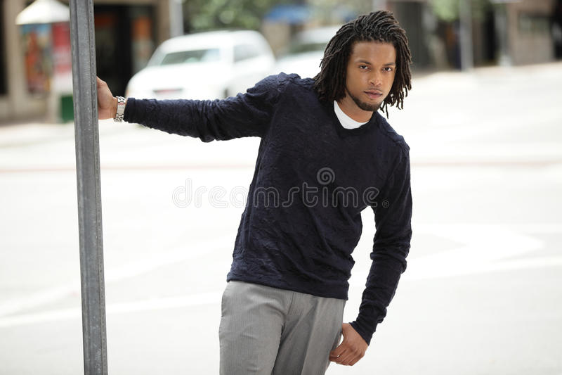 Download Jamaican Man Hanging From A Pole Stock Image - Image: 24987393