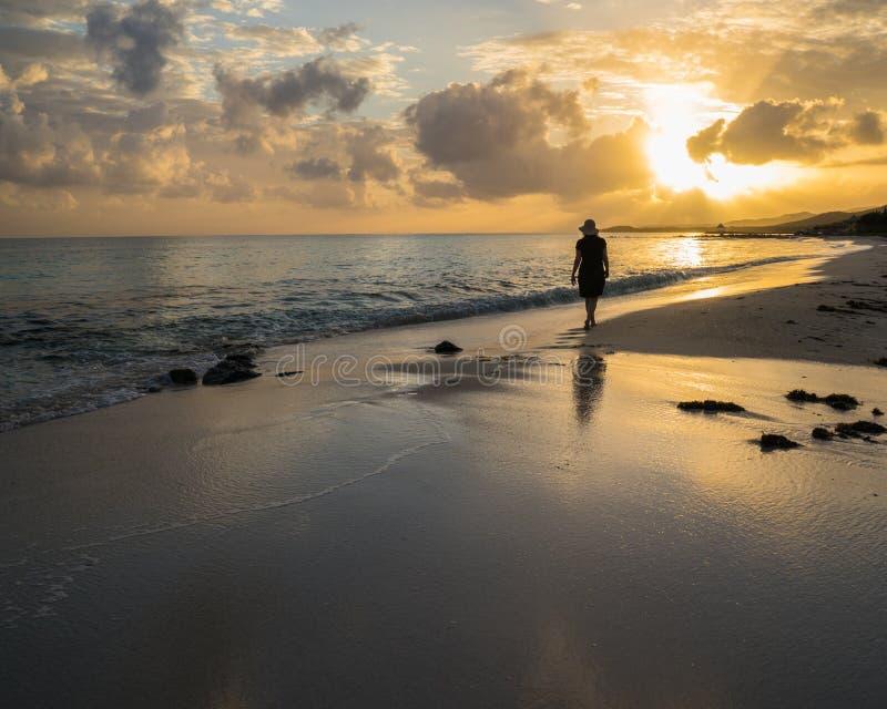 Jamaikanischer entferntstrand mit dem silhouettierten Frauengehen stockfotos