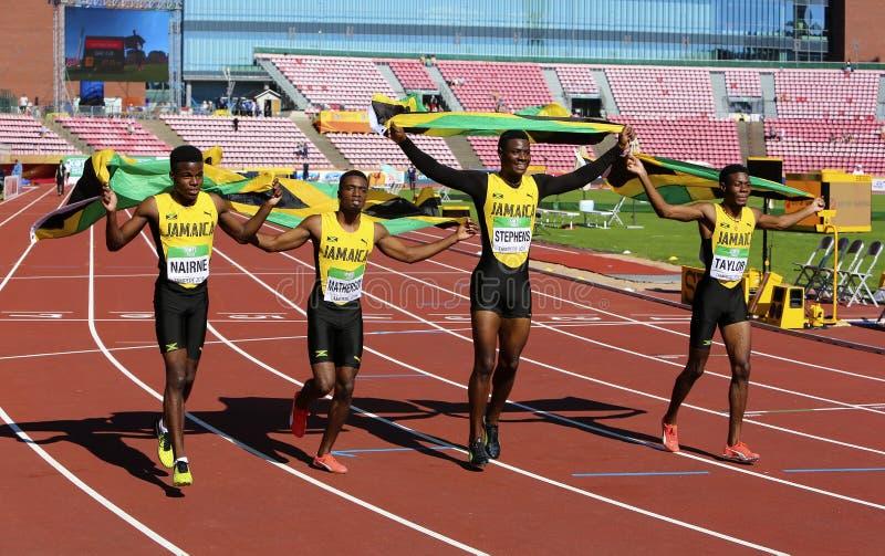 Jamaikanisches 4x100-Staffel-Team, das mit Flaggen das Gewinnen des Silbers auf der Meisterschaft IAAF-Weltu20 in Tampere, Finnla stockfoto