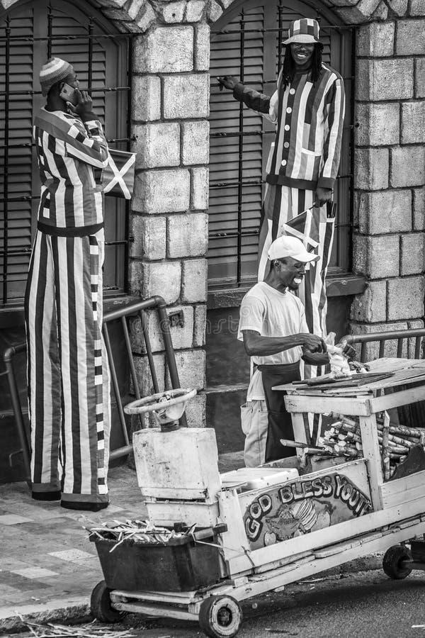 Jamaikanska arbetare - maskot och en försäljare för frukt för sockerrotting - på trottoaren på HipStripen på Margaritaville Monte fotografering för bildbyråer
