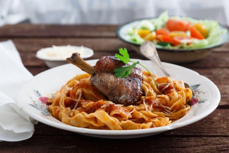 Jambe braisée de lapin en sauce tomate avec les pâtes faites maison, fond rustique foncé image stock