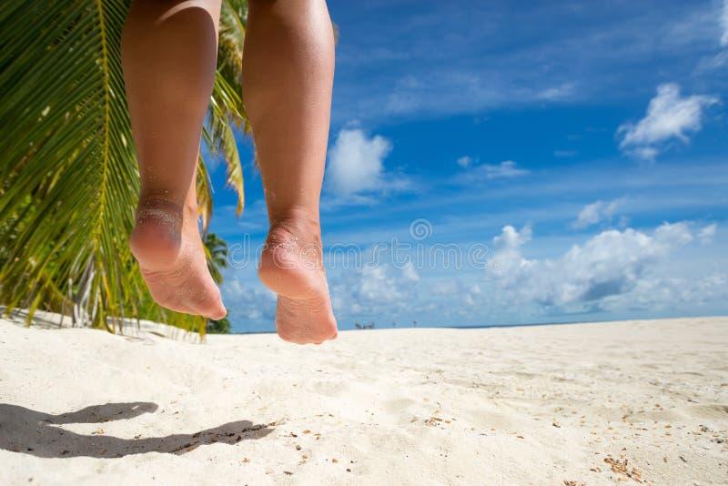 Jambe de femme sur une oscillation à la plage tropicale de mer photo libre de droits
