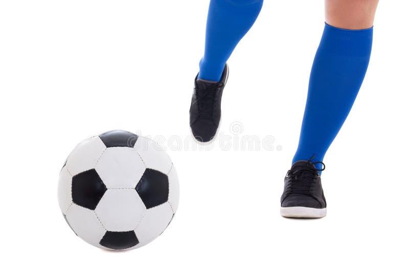 Jambe de footballeur dans les manchettes bleues donnant un coup de pied la boule d'isolement sur le wh image stock