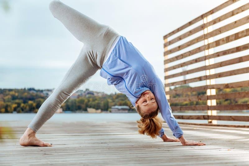 Jambe de levage de femme dans la pose orientée vers le bas de yoga de chien photos libres de droits