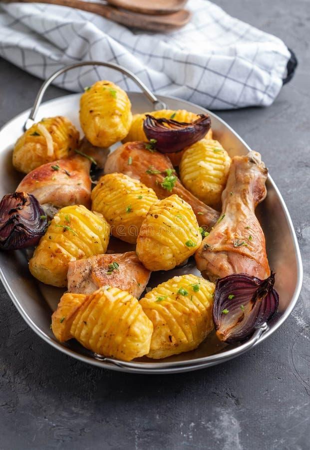 Jambe de poulet rôti avec des pommes de terre cumin et ail sur le fond noir Copiez l'espace image libre de droits