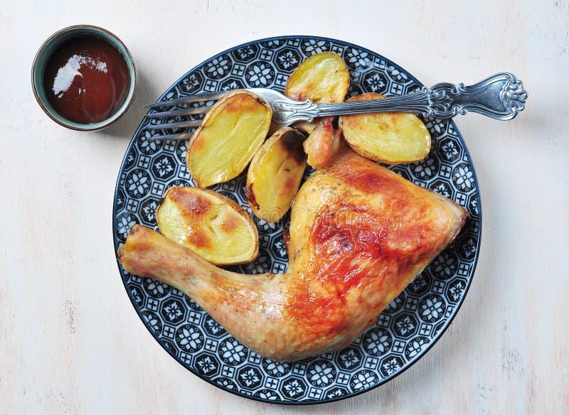 Jambe de poulet rôti avec les pommes de terre cuites au four images stock